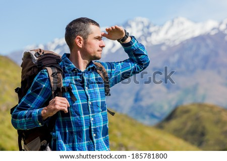close up portrait of hiker looking at the horizon in the mountains on sunny day
