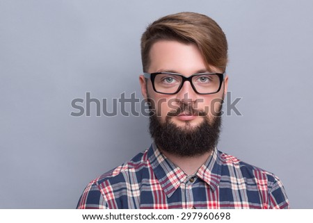 Close-up portrait of hipster bearded man. Happy man with up-to-date hairstyle posing in glasses near grey background.