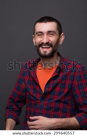 Close-up portrait of hipster bearded man on dark grey. Man in plaid shirt and T-shirt laughing and showing his teeth.