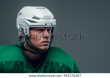 Close up portrait of hockey player with a helmet on grey background.