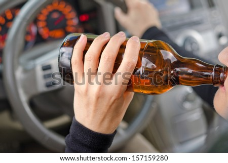 Close up portrait of human drinking alcohol while driving - stock photo