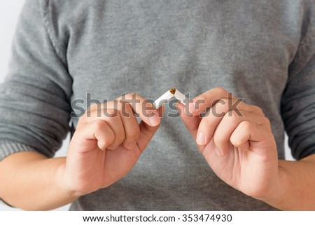 Close up portrait of human hands breaking down cigarette to pieces. Studio shot selective focus isolated on white background. Quit smoking addiction concept. Stop smoking message - stock photo