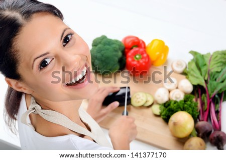 Close up portrait of indian woman looking over her shoulder while cooking and preparing food in the kitchen - stock photo
