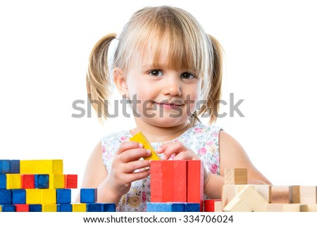 Close up portrait of infant playing building game with wooden blocks at table.Isolated on white background. - stock photo