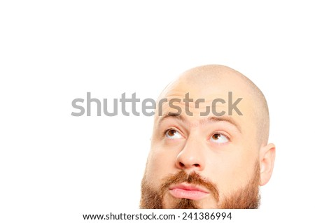 Close up portrait of interested young bearded man looking up isolated on white background - stock photo