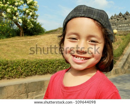 close up portrait of kid in green nature smiling to the camera - stock photo