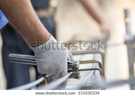 Close up portrait of laborer hands holding armature on construction site  - stock photo