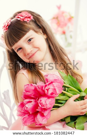 Close up portrait of little adorable girl holding pink tulips in her hands.