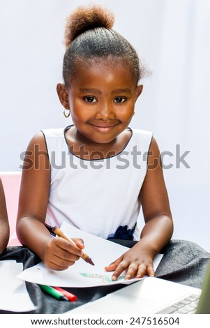 Close up portrait of little African girl drawing with crayons at desk.Isolated on light background. - stock photo