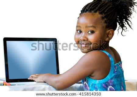 Close up portrait of little african girl typing on laptop.Isolated on white background. - stock photo