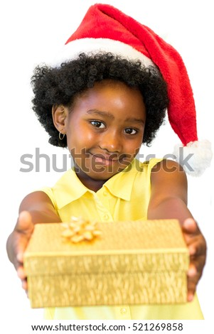 Close up portrait of little african girl wearing red christmas hat holding golden box.Isolated on white background.