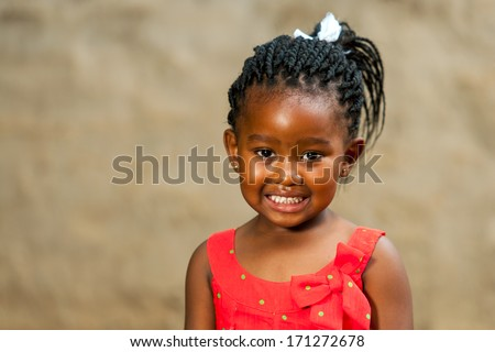 Close up portrait of little african girl with braided hair outdoors. - stock photo