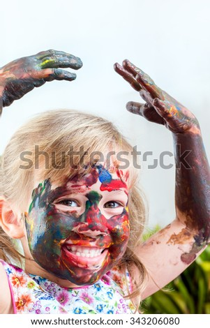 Close up portrait of little girl covered with color paint raising hands above head.