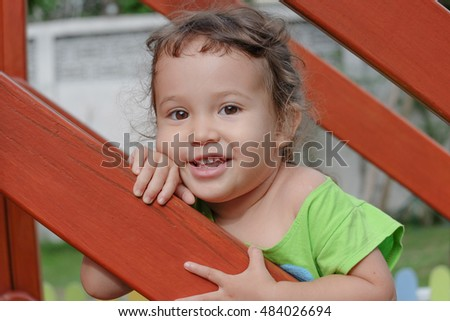 Close up portrait of little girl playing on children playground in summer. Smiling beautiful little girl.