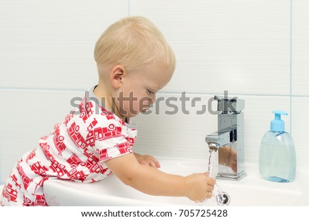 Close-up portrait of little white Caucasian boy toddler one year old washing hands in bathroom and looking surprised excited, playing with water.