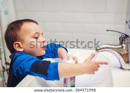 Close-up portrait of little white Caucasian boy toddler two years old washing hands in bathroom and looking surprised excited, playing with water and foam