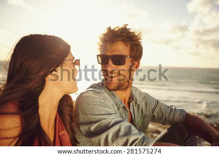 Close-up portrait of loving young couple looking at each other at the beach. Romantic caucasian couple in love on summer holiday. - stock photo