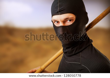 Close up portrait of male ninja in black mask covered his face - stock photo