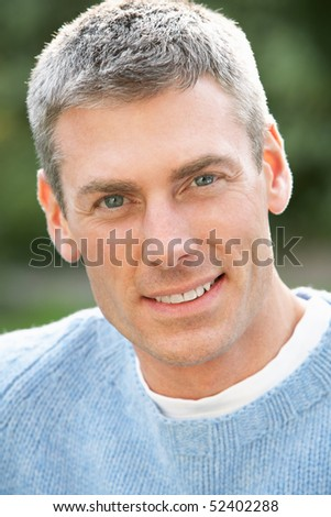 Close Up Portrait Of Man Standing Outside In Autumn Landscape - stock photo