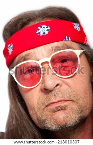 Close Up Portrait of Man with Stubble Wearing Headband and Rose Colored Glasses Resembling an Aging Hippy