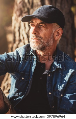 Close up portrait of mature man wearing cap looking away while sitting by a tree. Senior man with beard outdoors on a summer day. - stock photo