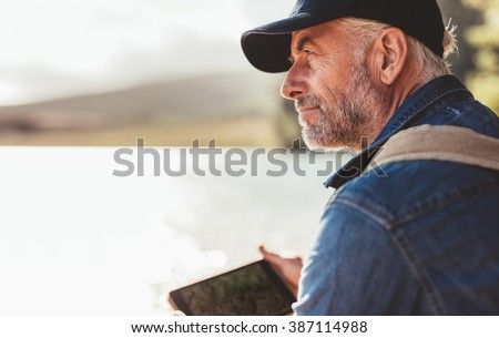 Close up portrait of mature man wearing cap sitting at a lake and looking at a view. Senior caucasian man with beard.