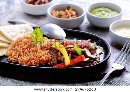 close up portrait of mexican beef fajitas with flour tortillas and rice - stock photo