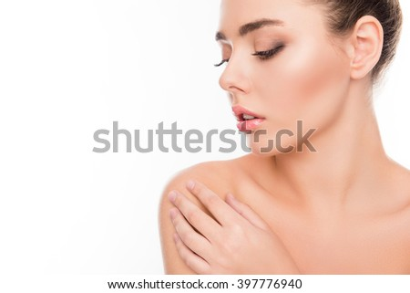 Close up portrait of minded woman touching her shoulder on white background - stock photo