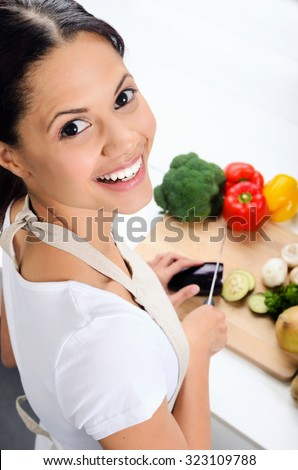 Close up portrait of mix race woman cooking and preparing food in the kitchen