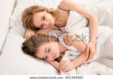 Close up portrait of mom and daughter sleeping lovely in bed