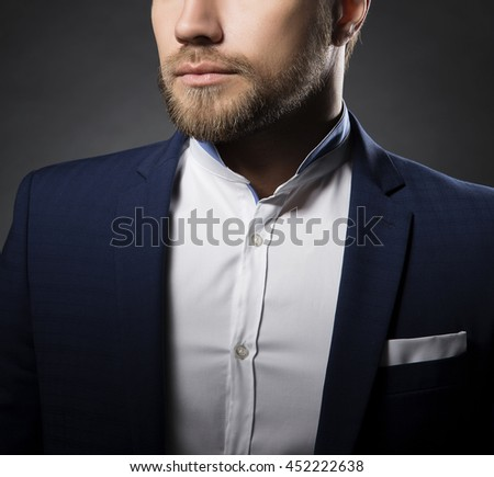 Close-up portrait of of handsome stylish caucasian young man in elegant blue suit with perfect hair style.  - stock photo