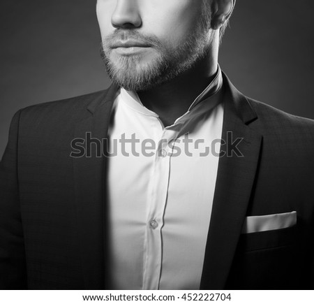 Close-up portrait of of handsome stylish caucasian young man in elegant blue suit with perfect hair style. Black and white - stock photo
