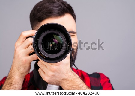 Close up portrait of photographer taking pictures with digital camera - stock photo