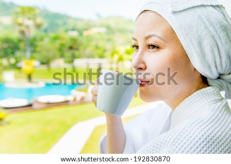 Close-up portrait of Pretty asian Young woman in the towel hat with the cap of coffee against  of  the big green garden and pool - stock photo