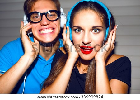 Close up portrait of pretty crazy couple  having fun at night student part, funny emotions, hipster style bright makeup, listening music at earphones, bright outfits, night image with flash. - stock photo