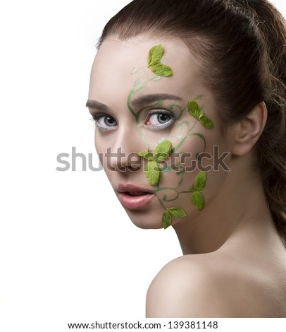 close-up portrait of pretty girl with nacked shoulders, creative fresh summer make-up with mint leaves - stock photo