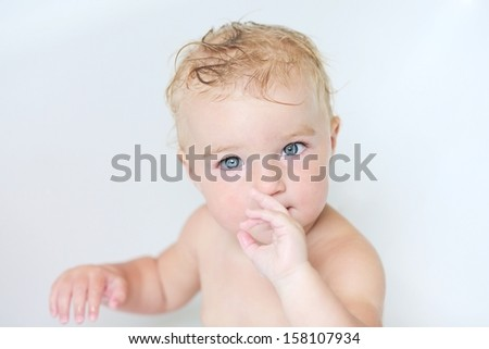 Close up portrait of pretty little baby girl sitting in a bath sucking on her finger - stock photo