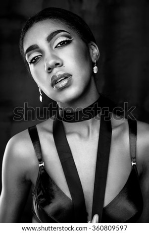 Close up portrait of pretty young african american woman wearing red bra on wooden background. black and white photo