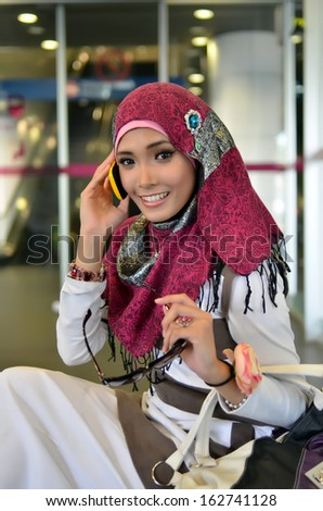 Close-up portrait of pretty young Asian business in the train station  - stock photo