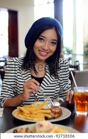 Close-up portrait of pretty young Asian eating at restaurant - stock photo