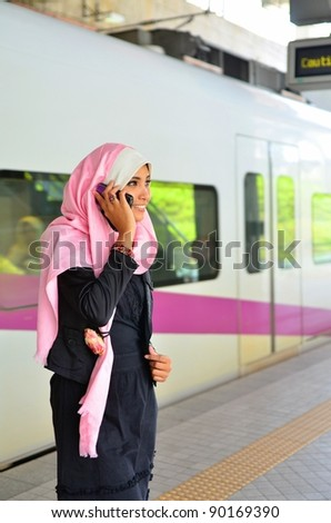 Close-up portrait of pretty young Asian Muslim making a phone call  in the train station