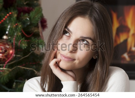 Close-up portrait of pretty young woman  in Christmas interior in front of fireplace - stock photo