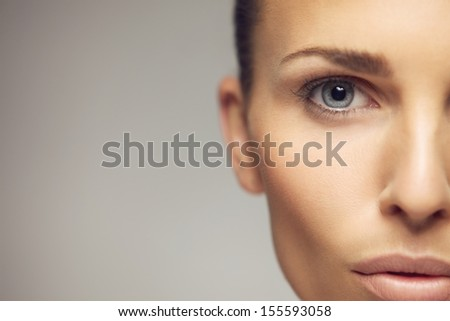 Close-up portrait of pretty young woman with perfect healthy skin and beautiful eyes.  Half face of pretty young female against gray background - stock photo