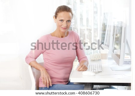 Close-up portrait of professional marketing assistant working on computer at her workplace.  - stock photo