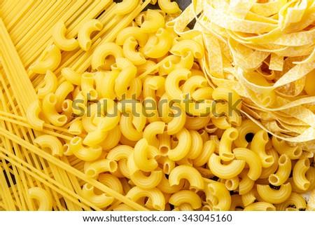 close up portrait of raw homemade italian pasta, macaroni, spaghetti, and fettuccine - stock photo