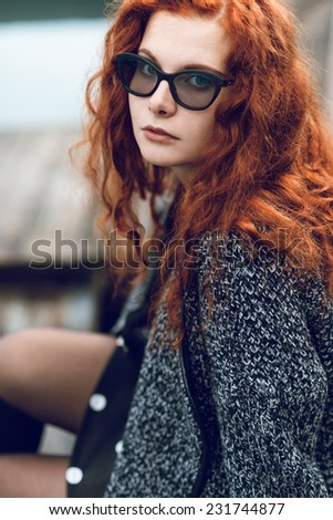 Close-up portrait of red-haired girl in glasses