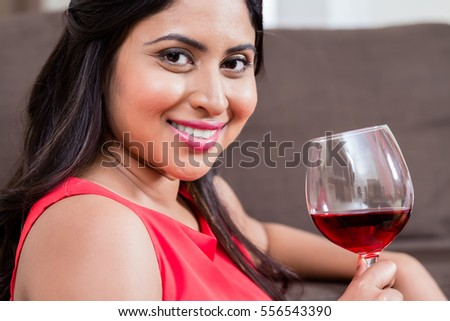 Close-up portrait of relaxed beautiful young woman drinking red wine at home