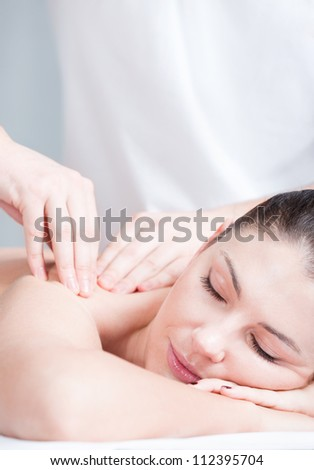 Close-up portrait of relaxing woman having massage on her shoulder - stock photo
