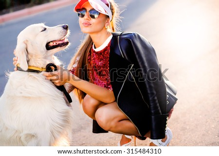 Close-up portrait of rich man playing outdoor with her dog on the street,dog licks his master,girl hugging her puppy,golden labrador puppy,funny mood,positive emotions,kissing lips,walking alone,urban - stock photo