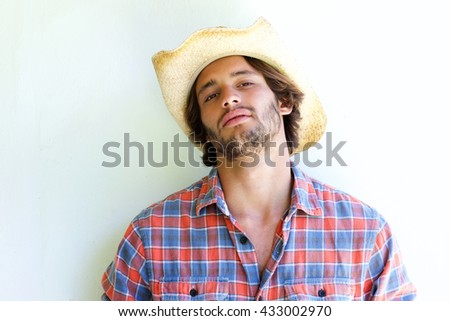 Close up portrait of rugged young man wearing cowboy hat - stock photo
